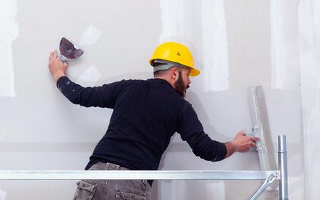 Image d'un platrier en train d'enduire un mur